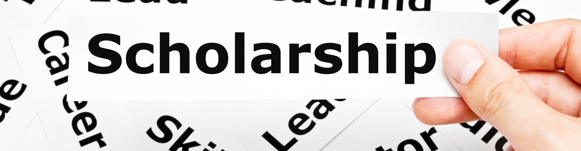 Hand holding a piece of paper with the word Scholarship printed on it above other related words in the background.