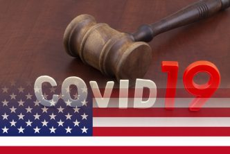 Wooden judge gavel with letters covid19 on table and usa flag. Concept of quarantine and law against covid-19.