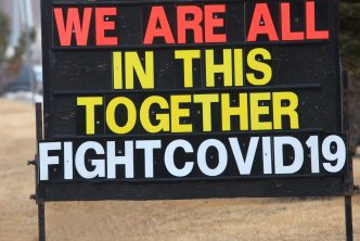 A sign or billboard in front of a business that states we are all in this together fight Covid-19.