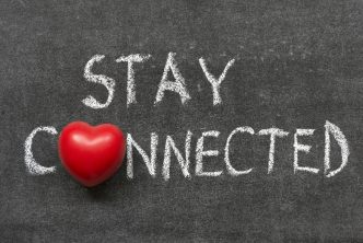 stay connected phrase handwritten on blackboard with heart symbol instead of O