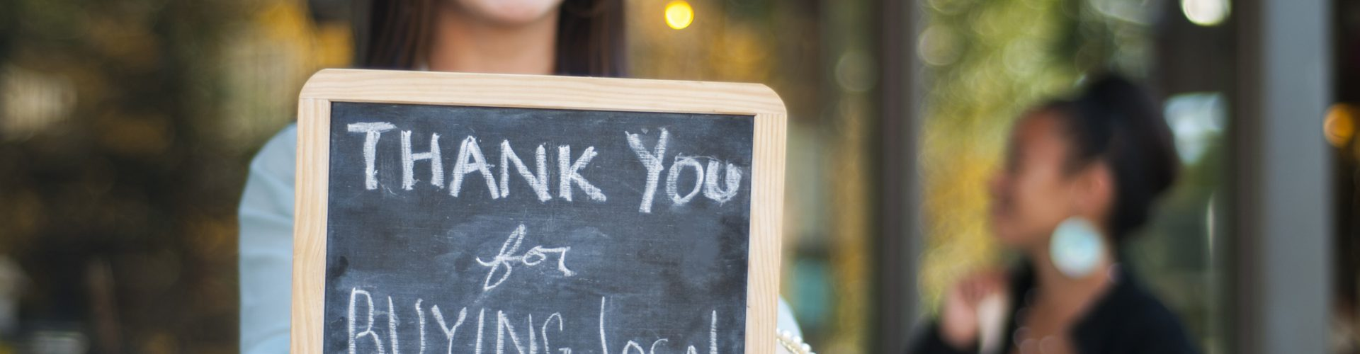 """Young business owner holding a """"Thank You for Buying Local"""" sign in front of her store with shopper in the background."""